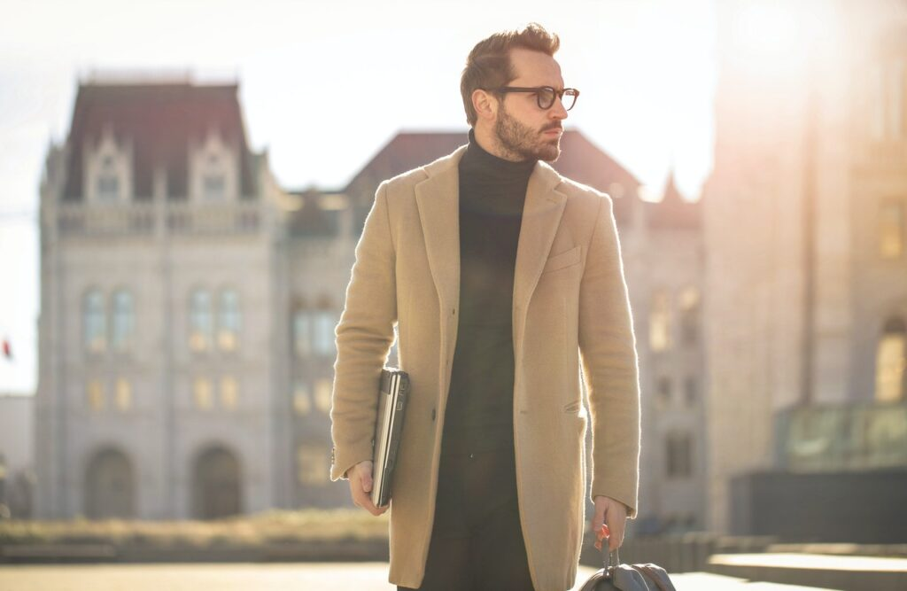 A man on his way to work wearing a black turtleneck and a coat