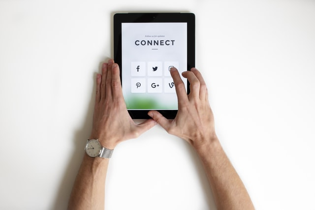 a person holding a tablet with social media shortcuts
